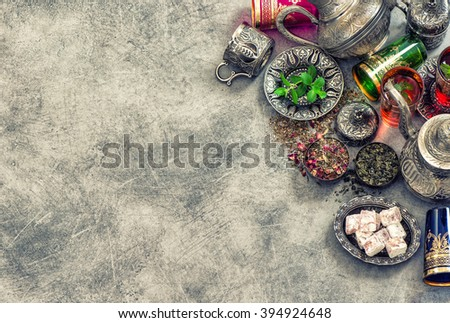Tea table place setting with colorful glasses. Oriental hospitality concept. Vintage style toned picture - stock photo