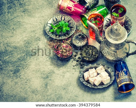 Tea table place setting with colorful glasses. Vintage style toned picture - stock photo