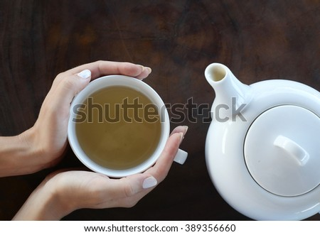 Tea time. Girl holding a cup of tea on the table