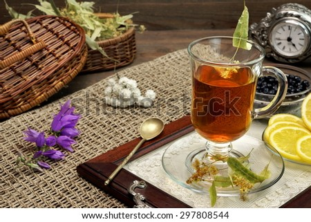 Tea Time Scene In The  Rustic Style. Glass Teacup With Lime Tree Herbal Green Tea, blueberries,  lemon, Herbs Leafs In The Basket,  Vintage Spoon And Clock On The Rough Old Wooden Table - stock photo