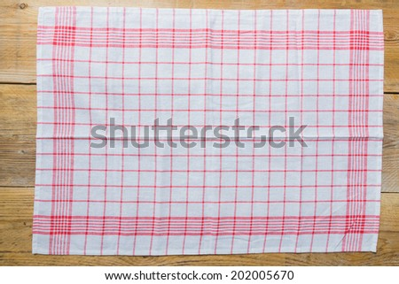 Tea towel on rustic wooden background. - stock photo