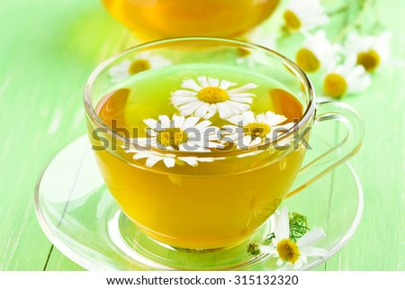 Tea with chamomile flowers in glass cup, close up view - stock photo