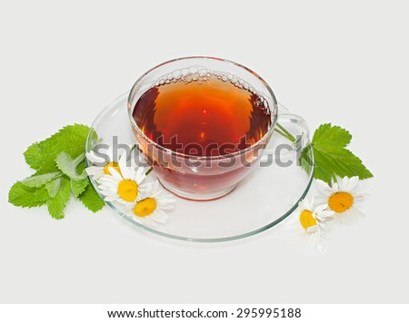 Tea with chamomile, mint leaves and currant on a gray background. - stock photo