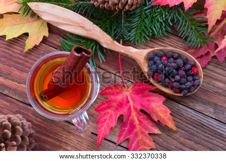 tea with cinnamon and lemon, colorful autumn leaves of maple, hawthorn berries in a wooden spoon, ripe apples and spruce branches with cones on a wooden table close-up view from above, selective focus - stock photo