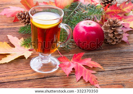 tea with cinnamon and lemon, ripe apples, red autumn maple leaves, fir branch and pine cones on wooden table closeup - stock photo