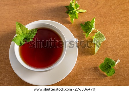 tea with currant leaves, a white Cup on a wooden table