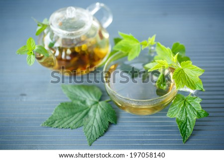 tea with currant leaves on a wooden table