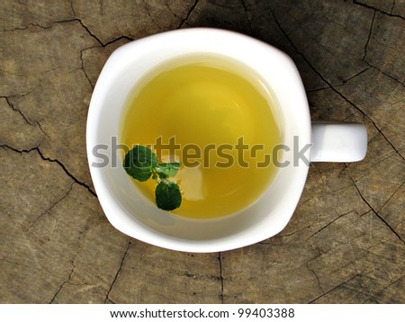 Tea with green leaf in white cup on wood - stock photo