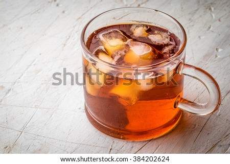 Tea with ice on the white scratched table