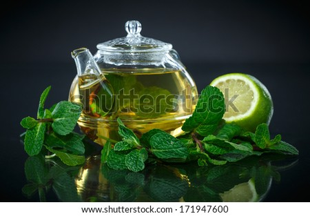 tea with lemon and mint on black background - stock photo
