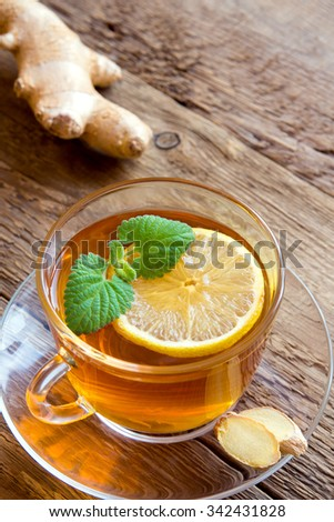 Tea with lemon, ginger and mint leaves in transparent cup over rustic wooden background - stock photo