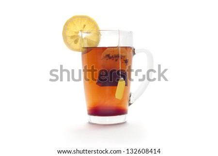 Tea with lemon in a glass cup on a white background. Tea bag