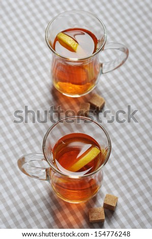 Tea with lemon in glass cups on checkered napkin