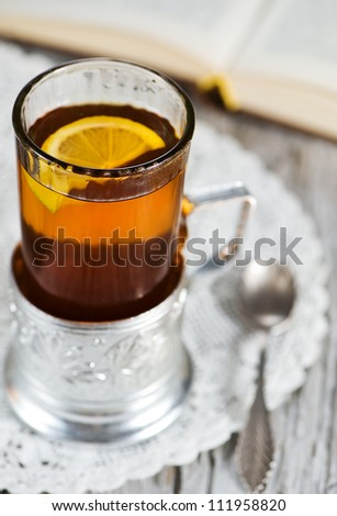 Tea with lemon in the glass-holder and book
