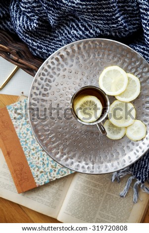 Tea with lemon on a background of blankets and books. Top view, selective focus - stock photo