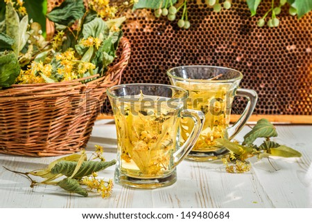 Tea with lime and honey served in the garden at summer - stock photo