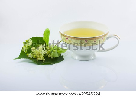 tea with lime, Linden flowers and leaves, white background - stock photo