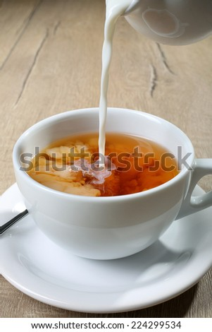 tea with milk pour - stock photo