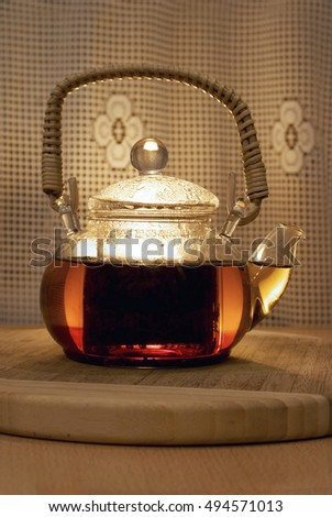 Tea with mint in a glass teapot on a support, selective focus