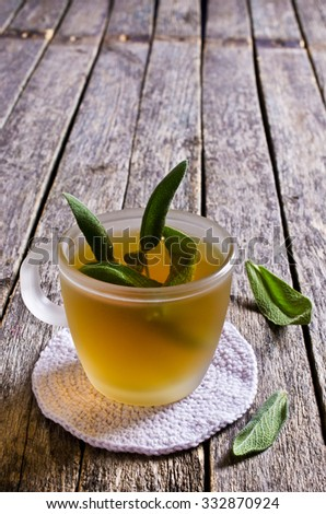 Tea with sage leaves in a glass Cup on a wooden surface - stock photo