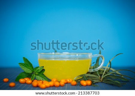 Tea with sea-buckthorn on a wooden table