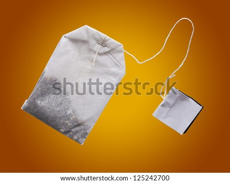 teabag with a label on the brown-yellow background