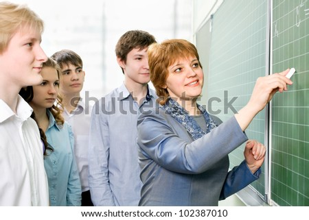 Teacher and a group of students in the class - stock photo