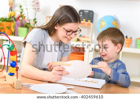 Teacher and Child Playing at Kindergarten Didactic Games - stock photo
