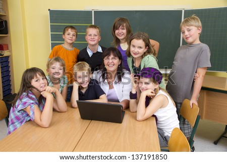 Teacher and children in a yellow classroom. They all looking to camera. The children are around the teacher, she is sitting in the middle. In front of the people you see a notebook. - stock photo
