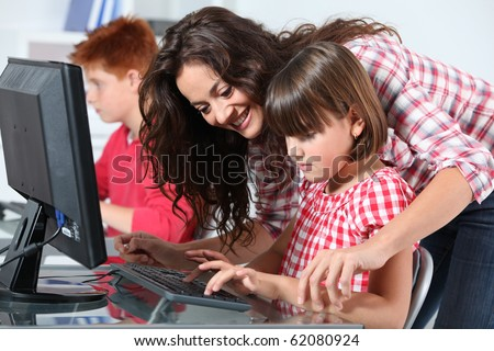 Teacher and children learning to use computer