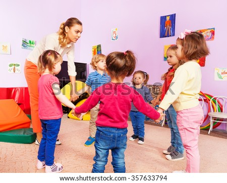 Teacher and group of kids in kindergarten  - stock photo