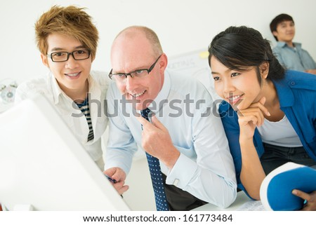 Teacher and his students looking at computer screen together - stock photo