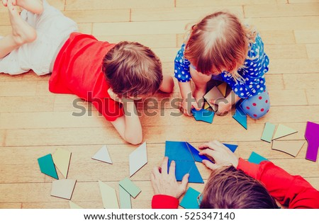 teacher and kids playing with geometric shapes