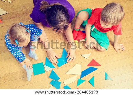 teacher and kids playing with geometric shapes, early learning - stock photo