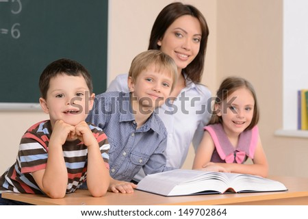 Teacher and pupils. Confident young teacher sitting together with pupils and reading book - stock photo