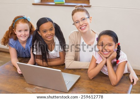 Teacher and pupils looking at laptop at the elementary school - stock photo