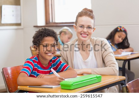 Teacher and pupils smiling at camera in classroom at the elementary school