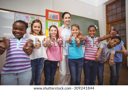 Teacher and pupils smiling in classroom at the elementary school - stock photo
