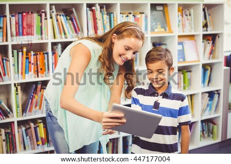 Teacher and school boy using digital tablet in library at school