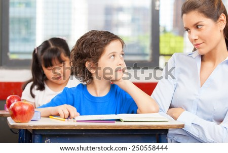 Teacher and schoolboy looking each other in primary classroom. - stock photo