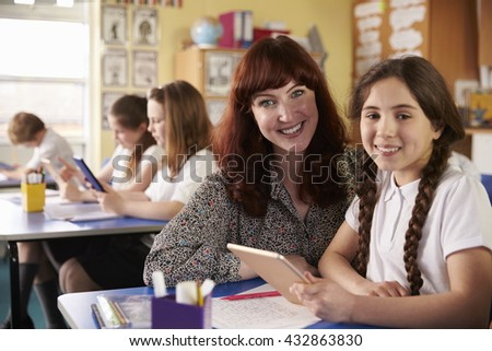 Teacher and schoolgirl using tablet computer look to camera - stock photo