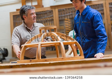 Teacher and student at a workbench in a woodworking class talking about a frame - stock photo