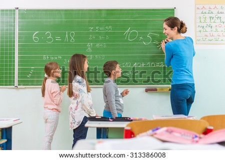 Teacher and student at the blackboard, math class - stock photo