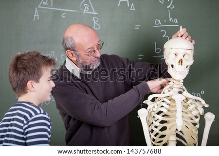 Teacher and student during an anatomy class - stock photo
