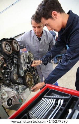 Teacher and student in auto mechanics training class - stock photo