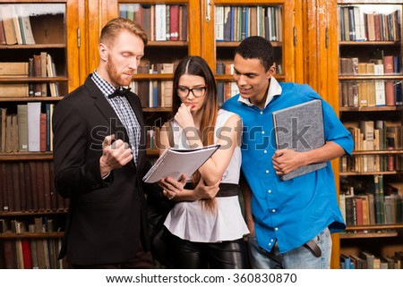 Teacher and students in library - stock photo