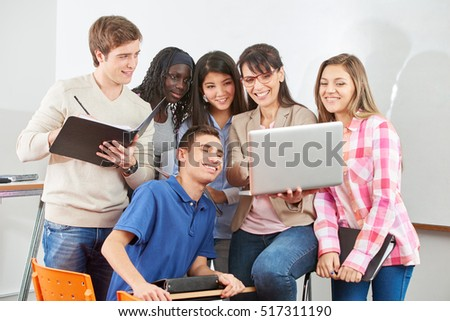 Teacher and students interact with laptop in class