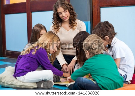 Teacher and students reading book on floor in preschool - stock photo