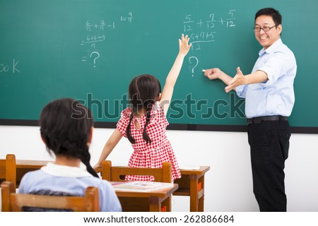 teacher asking question with children  in classroom - stock photo