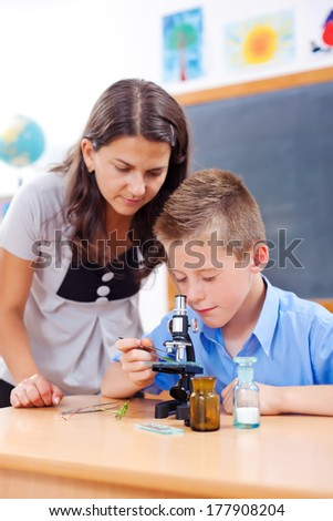 Teacher assisting schoolboy looking into microscope in biology class - stock photo